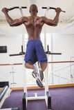 Male body builder doing pull ups at gym Royalty Free Stock Photo