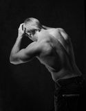 Male bodybuilder. Rear view of male bodybuilder with bare torso posing with hands on head, black background Stock Images