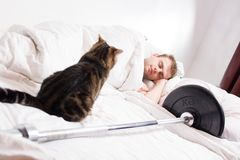 A male bodybuilder is asleep after training with a cat and a barbell on a white background. A male bodybuilder is asleep after training with a cat and a barbell Stock Photos