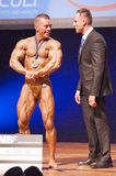 Male bodybuilder celebrates his championship victory on stage wi Royalty Free Stock Image