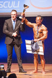 Male bodybuilder celebrates his championship victory on stage wi Royalty Free Stock Photos