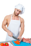 Male bodybuilder chef cuts a tomato. Royalty Free Stock Image