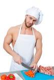 Male bodybuilder chef cuts a tomato. Royalty Free Stock Image
