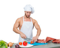 Male bodybuilder chef cuts a tomato. Royalty Free Stock Photography