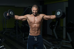 Male Bodybuilder Doing Heavy Weight Exercise For Shoulders Stock Photo