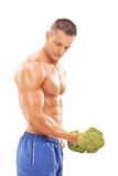 Male bodybuilder exercising with a broccoli dumbbell Stock Photography