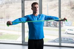 Male Bodybuilder Exercising in Gym With Resistance Band stock image