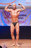Male bodybuilder flexes his muscles and shows his best physique Stock Photography