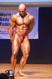 Male bodybuilder flexes his muscles to show his physique Royalty Free Stock Image