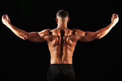 Male bodybuilder flexing muscles, back view Royalty Free Stock Images