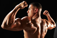 Male bodybuilder flexing muscles, side view Stock Photos