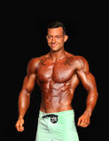 Male Bodybuilder with Green Trunks and Tattoos Stock Photo