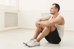 Male bodybuilder having rest after workout. Pensive athletic young man having rest after bobybuilding training, sitting on the floor at white gym interior, copy Royalty Free Stock Photo