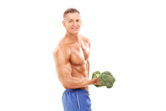 Male bodybuilder holding a broccoli dumbbell Stock Images