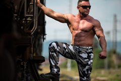 Male Bodybuilder Holding On To Train Royalty Free Stock Image