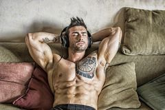 Male bodybuilder listening to music on sofa. Handsome shirtless muscular bodybuilder man listening to music with headphones while sitting on couch stock photo