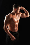 Male bodybuilder looking at his flexing muscles Stock Image