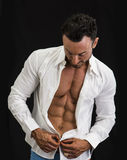 Male bodybuilder opening his shirt revealing muscular torso. On black background Royalty Free Stock Photos