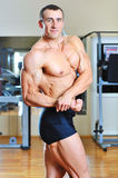 Male bodybuilder posing in gym Stock Photo
