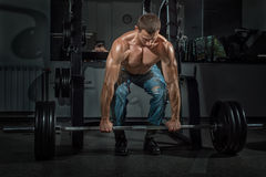 Male bodybuilder raises the bar. Royalty Free Stock Photography