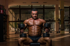 Male bodybuilder resting after doing heavy weight exercise Royalty Free Stock Photos