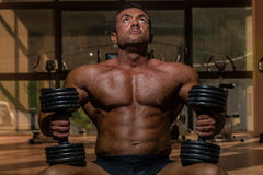 Male bodybuilder resting after doing heavy weight exercise. Male body builder resting after doing heavy weight exercise Stock Image