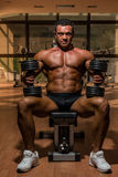 Male bodybuilder resting after doing heavy weight exercise. In gym Stock Images