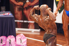 Male bodybuilder shows his best back double biceps pose Royalty Free Stock Images