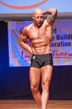 Male bodybuilder shows his best at championship on stage Stock Photos