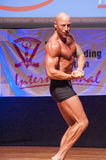 Male bodybuilder shows his best at championship on stage Stock Photography