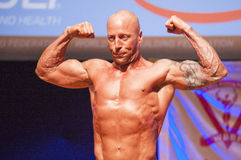 Male bodybuilder shows his best at championship on stage Stock Images