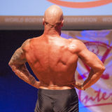Male bodybuilder shows his best at championship on stage Royalty Free Stock Photos