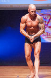 Male bodybuilder shows his best at championship on stage Stock Photo
