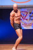 Male bodybuilder shows his best at championship on stage Royalty Free Stock Image