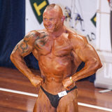 Male bodybuilder shows his best lats spread pose on stage Stock Images