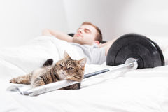 A male bodybuilder is sleep after training with a cat and a barb. A male bodybuilder is asleep after training with a cat and a barbell on a white Royalty Free Stock Photography
