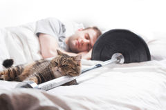 A male bodybuilder is sleep after training with a cat and a barb. A male bodybuilder is asleep after training with a cat and a barbell on a white Stock Photos