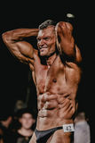 Male bodybuilder straining press, hands behind head Royalty Free Stock Images