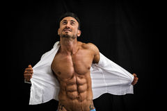 Male bodybuilder taking off his shirt revealing muscular torso. On black background Royalty Free Stock Photo