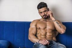 Male bodybuilder talking on cellphone on sofa Royalty Free Stock Photos