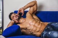 Male bodybuilder talking on cellphone on sofa Stock Photo