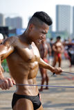 The male bodybuilder use the tensioner Royalty Free Stock Photography