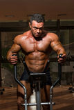 Male bodybuilder using the elliptical machine Royalty Free Stock Photo