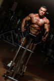 Male bodybuilder using the elliptical machine Stock Photo