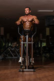 Male bodybuilder using the elliptical machine Royalty Free Stock Photography