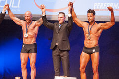 Male bodybuilders celebrate their championship victory on stage Stock Images