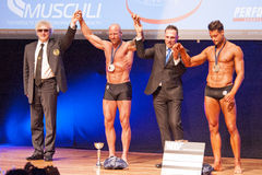 Male bodybuilders celebrate their championship victory on stage Stock Photo