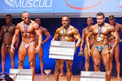 Male bodybuilders celebrate their championship victory on stage Royalty Free Stock Images