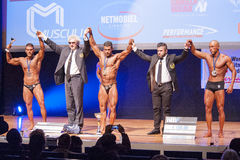 Male bodybuilders celebrate their championship victory on stage Royalty Free Stock Photos