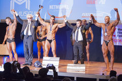 Male bodybuilders celebrate their championship victory on stage Stock Photos